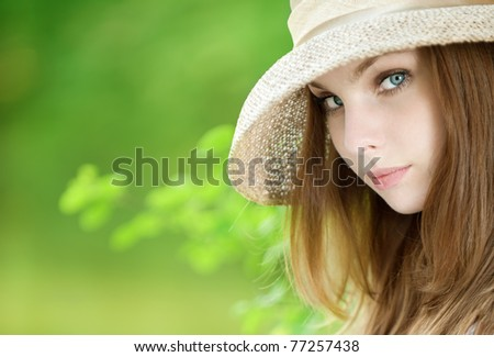 beautiful young woman in a hat on green background