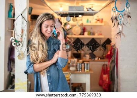 Beautiful young woman in a hipster kitchen talks to her phone dressed in a jeans and a white shirt
