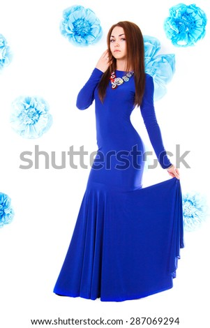 Beautiful young woman in a long blue evening dress at the background of the cyan flowers - stock photo