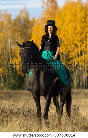 Beautiful young woman in a long dress and hat riding on a black horse. Autumn, yellow leaves, field and forest.