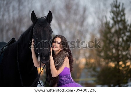 Beautiful young woman in a long purple dress with a black horse