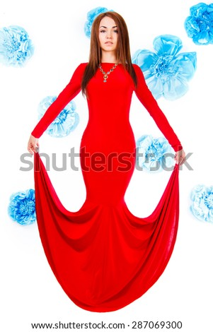 Beautiful young woman in a long red evening dress at the background of the cyan flowers - stock photo
