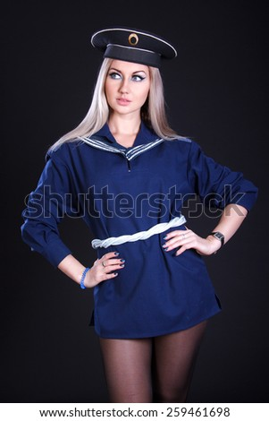 Beautiful young woman in a marine uniform over black background - stock photo