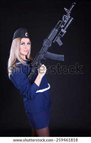 Beautiful young woman in a marine uniform with an assault rifle over black background - stock photo
