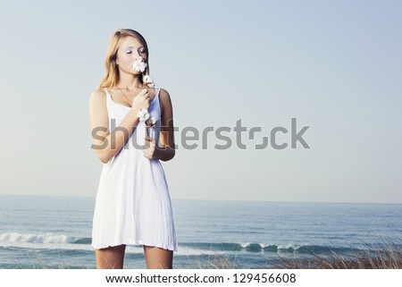 Beautiful young woman in a meadow holding and smelling a cotton plant - stock photo