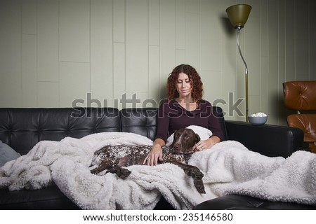 beautiful young woman in a modern living room with a dog - stock photo