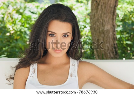 Beautiful young woman in a outdoor garden patio setting. - stock photo