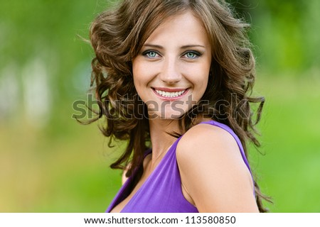 Beautiful young woman in a purple dress happily smiling, against green of summer park. - stock photo