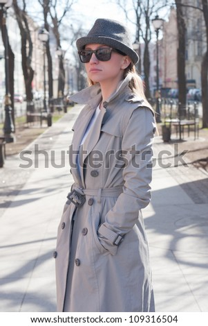 beautiful young woman in a raincoat on the street