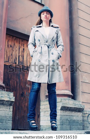 beautiful young woman in a raincoat on the street - stock photo