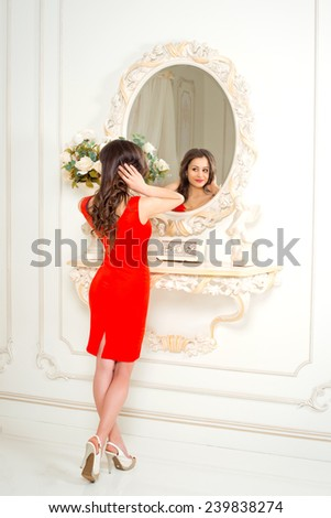 beautiful young woman in a red dress looking to the mirror. Studio. - stock photo
