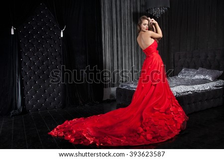 Beautiful young woman in a red dress, the background interior