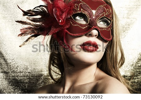 Beautiful young woman in a red mysterious venetian mask on a gold background