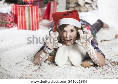 Beautiful young woman in a Santa hat lying on the floor near Christmas tree - stock photo