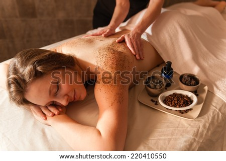 Beautiful young woman in a spa receiving a massage.