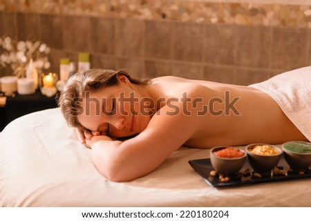 Beautiful young woman in a spa relaxing on a table waiting for a massage.
