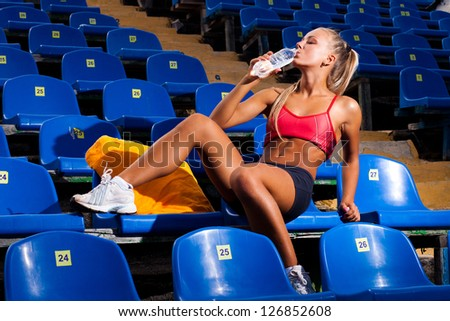 Beautiful young woman in a sports suit sitting on a seat and drink water from a bottle - stock photo