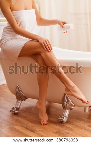 Beautiful young woman in a towel holding a bottle of cream and applying it on her leg while sitting on the bath, cropped - stock photo