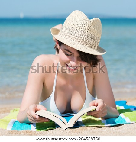 Beautiful young woman in a trendy straw hat lying sunbathing on a sunny tropical beach reading a book as she smiles happily while enjoying her summer vacation, close up frontal view - stock photo