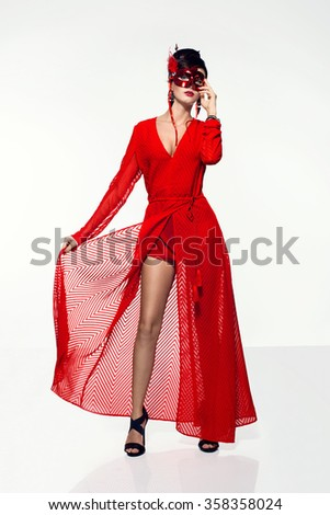 beautiful young woman in a very long red dress holding a mask. Carnival disco fashion photo - stock photo