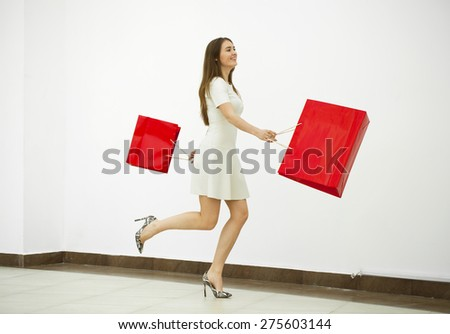 Beautiful young woman in a white dress, holding two red shopping bags walking in the shop - stock photo