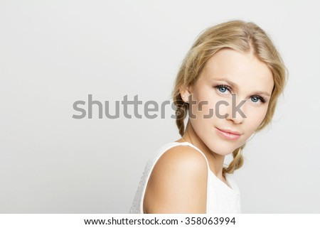 Beautiful young woman in a white dress. Isolated portrait of a woman on a gray background.