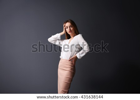 Beautiful young woman in a white shirt and pink skirt on grey wall background