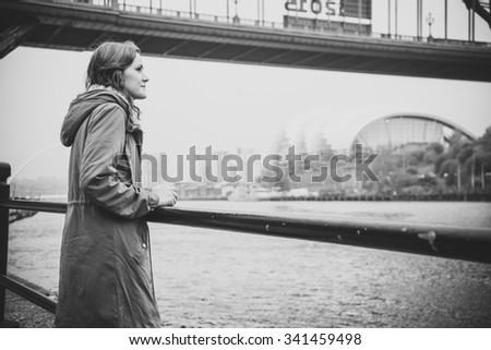 Beautiful young woman in a winter jacket, with brown hair and brown eyes, leaning on a post, staring out thoughtfully at the River Tyne. Tyne Bridge, Sage Gateshead, Baltic in distance. - stock photo