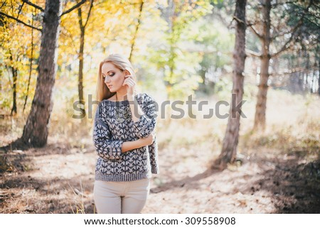 Beautiful young woman in a woolen sweater posing in an autumn forest - stock photo