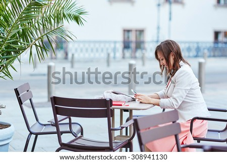 Beautiful young woman in an outdoor cafe using her mobile phone in Vienna, Austria - stock photo