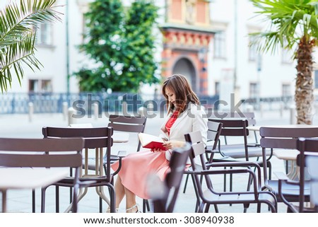 Beautiful young woman in an outdoor cafe writing in a notebook and planning her day in Vienna, Austria - stock photo