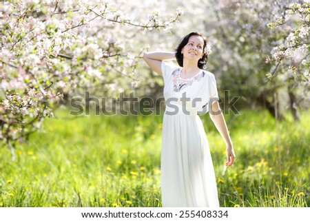 Beautiful young woman in apple blossom garden on a spring day - stock photo