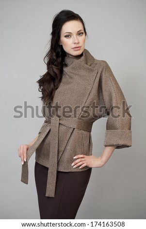 Beautiful young woman in autumn coat against gray background - stock photo