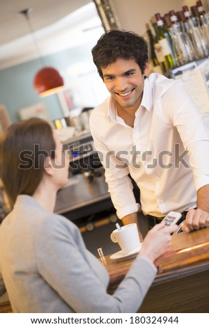 Beautiful young woman in bar speaking with bartender