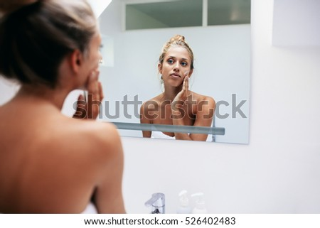 Beautiful young woman in bathroom looking in to mirror and applying  moisturizer on face   Beauty. Woman Bathroom Stock Images  Royalty Free Images   Vectors