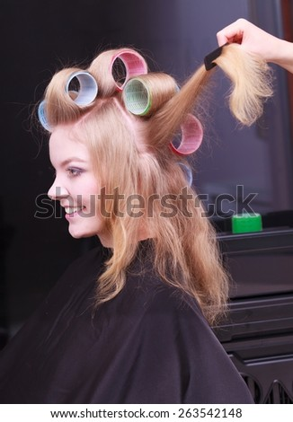 Beautiful young woman in beauty salon. Blond girl with hair curlers rollers by hairdresser. Hairstyle. - stock photo