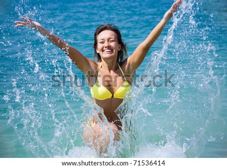 beautiful young woman in bikini bathing and splashing happily in the sea at the resort - stock photo