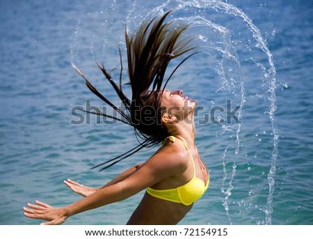 beautiful young woman in bikini bathing and splashing happily in the sea at the resort - stock photo