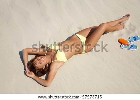 beautiful young woman in bikini lying and sunning on the beach under the bright sun - stock photo
