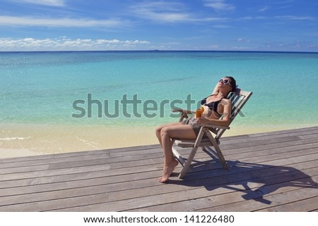 Beautiful young woman in bikini lying on a deckchair with a drink by the sea