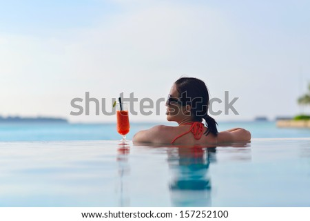 Beautiful young woman in bikini lying on a deckchair with a drink by the sea swimming pool and relax - stock photo