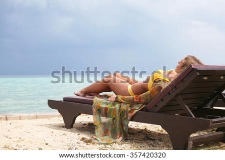 Beautiful young woman in bikini lying on tropical sea beach - stock photo