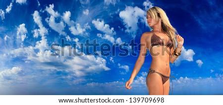 Beautiful young woman in bikini on bright blue shky background - stock photo
