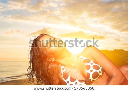 Beautiful young woman in bikini on the beach at sunset - stock photo