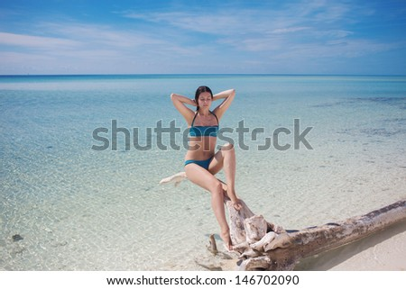 Beautiful young woman in bikini on the beach branch