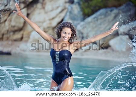 Beautiful young woman in bikini on the beach splashing water  - stock photo