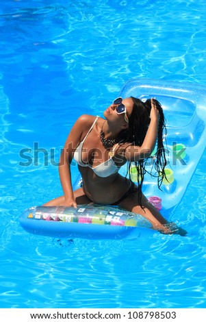 Beautiful young woman in bikini Relaxing in a pool