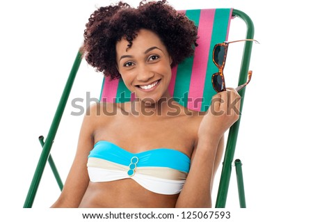 Beautiful young woman in bikini relaxing on a deckchair, holding her shades in hand.