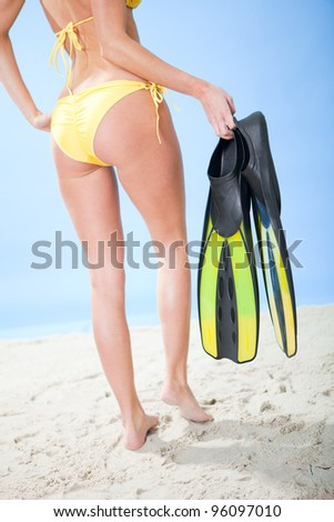Beautiful young woman in bikini with snorkel equipment at the beach - stock photo