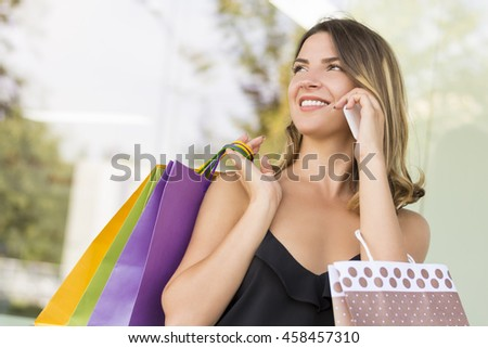 Beautiful young woman in black blouse talking on a mobile phone after doing shopping